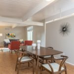 mid century rummer staged with wishbone dining chairs and a maple wood table to echo the mid century vibe