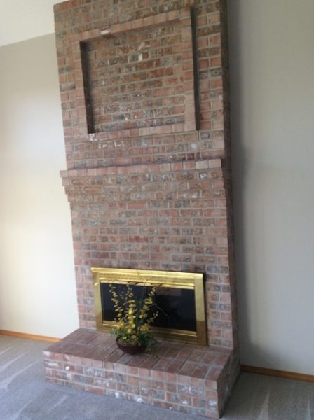 Before staging, this outdated brick and gold fireplace and surround was stale
